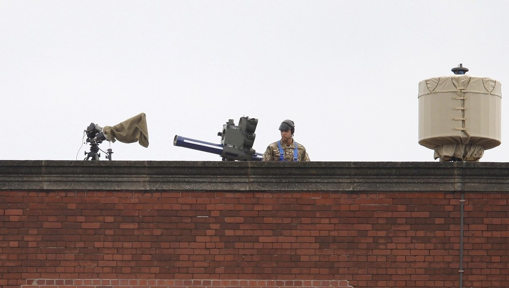 A member of the armed forces stands on duty next to an anti-aircraft missile battery, overlooking the Olympic Park in Stratford, east London